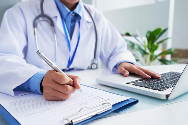 médico fazendo anotações ao lado de um notebook